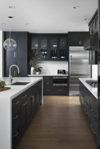 modern-kitchen-white-countertop-dark-cabinet-brushed-gold-accents-stainless-steel