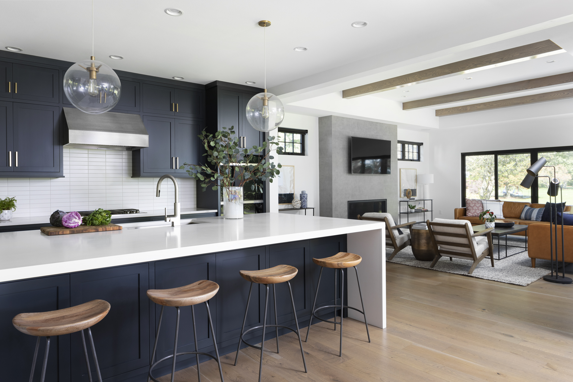 open-concept-kitchen-dark-cabinets-lakefront-home-glass-pendant-lights-brushed-gold
