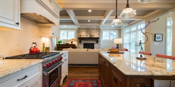 open-concept-kitchen-living-room-wood-beams-white-cabinets