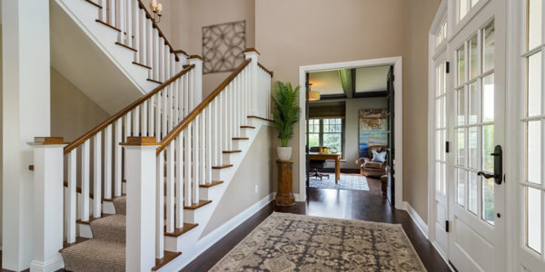 white-stained-wood-grand-staircase-entryway-dark-floors